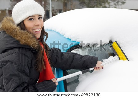 Beautiful young woman removing snow from her car.