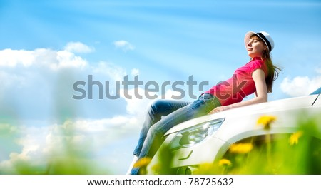 Beautiful young woman resting at bonnet of her car at flower field with blue cloudy sky in background