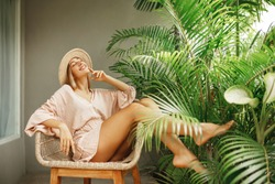Beautiful young woman resting at home in a wicker chair near the window with plants, smiling with closed eyes, wearing straw hat