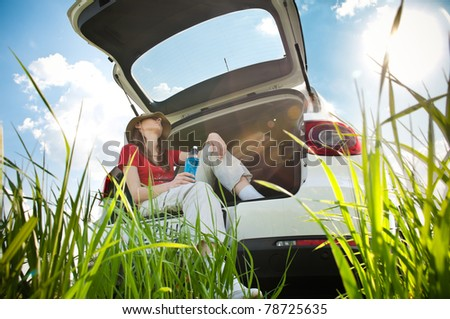 Beautiful young woman resting in boot of her car at  field with blue cloudy sky and sun in background