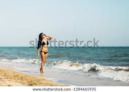 Beautiful young woman resting on the beach. She is standing and sunbathing near the sea, wearing black swimsuit and sunglasses.