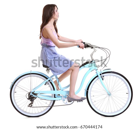 Beautiful young woman riding bicycle on white background