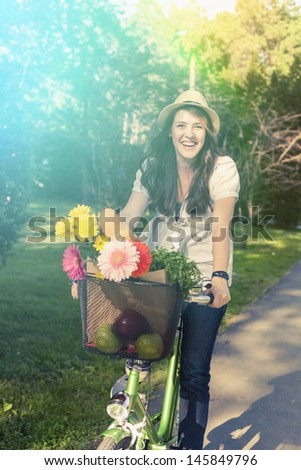 Beautiful young woman riding bicycle with hat on her head enjoying summer time.