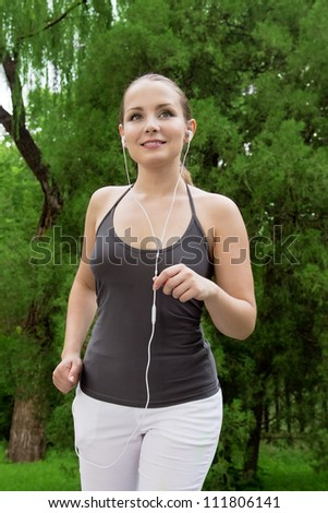 Beautiful young woman run and listen music in green park with music. Woman fitness jog workout wellness concept