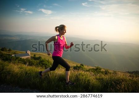 beautiful young woman run on a mountain path at sunrise #286774619