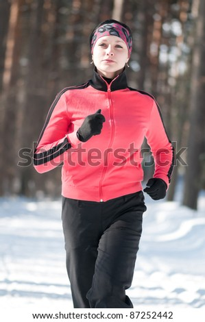 Beautiful young woman running at winter forest