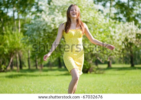 Beautiful young woman running in apple tree garden