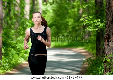 Beautiful young woman running in green park on sunny summer day
