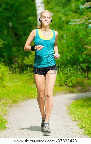 Beautiful young woman running in green park with music player