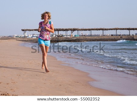 Beautiful young woman running on a beach