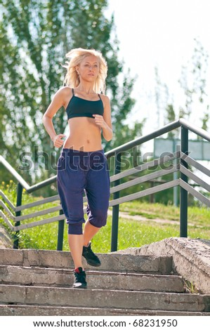 Beautiful young woman running  on city stairs