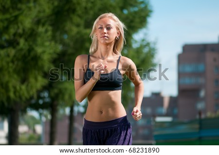 Beautiful young woman running over green city street landscape