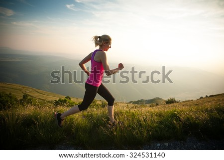 beautiful young woman runs on a mountain path at sunrise #324531140
