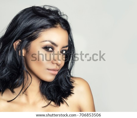 Beautiful young woman's face and sly cheeky look.