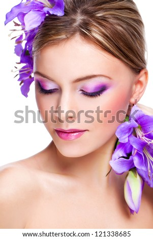 beautiful young woman's face with purple flowers and makeup