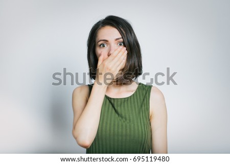 beautiful young woman scared, isolated on a gray background