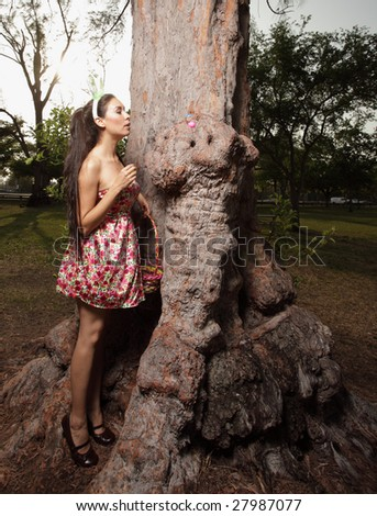 Beautiful young woman searching for Easter eggs in the park