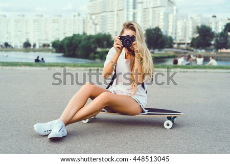 Beautiful young woman seating on skate and make self photo, street fashion lifestyle. outdoor portrait, vintage camera, hipster,longboard, hipster girl, closeup portrait