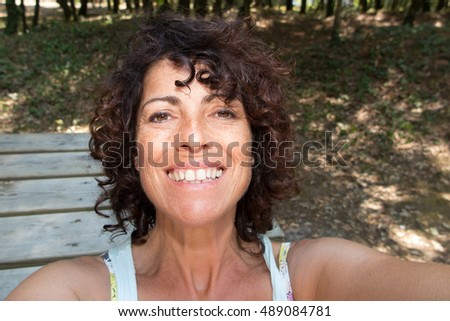 Beautiful young woman selfie in the park with a smartphone #489084781