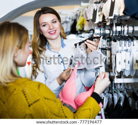 51cde41e3d Beautiful young woman seller assisting woman in choosing bra in underwear  store  777196477