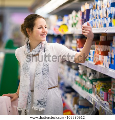 Beautiful young woman shopping for diary products at a grocery store/supermarket (color toned image)