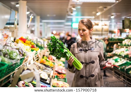 Beautiful young woman shopping for fruits and vegetables in produce department of a grocery store/supermarket (color toned image; shallow DOF)