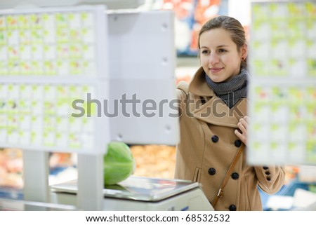 Beautiful young woman shopping for fruits and vegetables in produce department of a grocery store/supermarket - buying head cabbage (shallow DOF; color toned image)