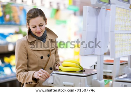Beautiful young woman shopping for fruits and vegetables in produce department of a grocery store/supermarket (shallow DOF; color toned image)