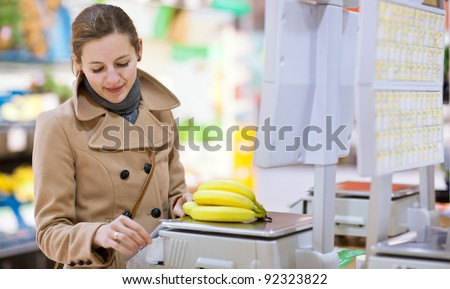 Beautiful young woman shopping for fruits and vegetables in produce department of a grocery store/supermarket - buying bananas (shallow DOF; color toned image)