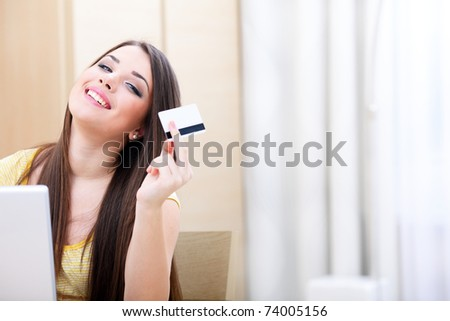 Beautiful young woman shopping on-line with credit card and laptop