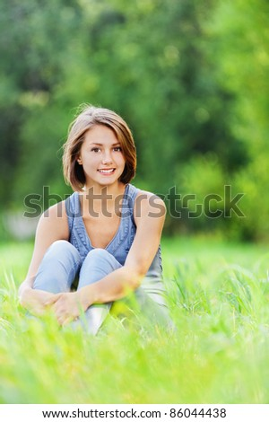 beautiful young woman short hair sitting alone grass meadow