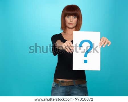 beautiful, young woman showing a question mark on a white piece of paper, on blue background