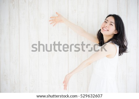 beautiful young woman showing, against white wooden wall