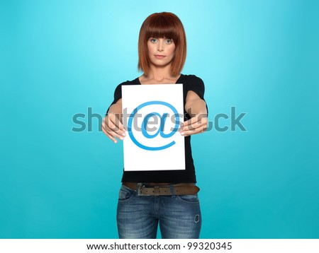 beautiful, young woman showing an at sign on a piece of paper, on blue background
