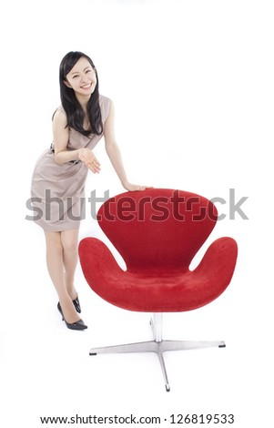 beautiful young woman showing modern red chair isolated on white background