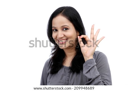 Beautiful young woman showing ok gesture against white