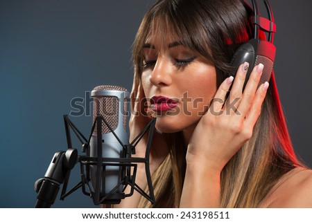 Beautiful young woman singer with the headphones standing in front of a microphone and sings with a slightly open mouth and eyes closed.