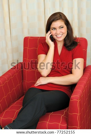 Beautiful young woman sits in a chair in her hotel room talking on her cell phone