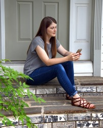 Beautiful young woman sits on the steps of her home holding her cell phone.  She has her eyes closed listening to her music.