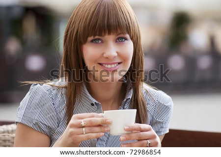 beautiful young woman sitting alone in a cafe outdoor and drinking a cup of tea looking in camera