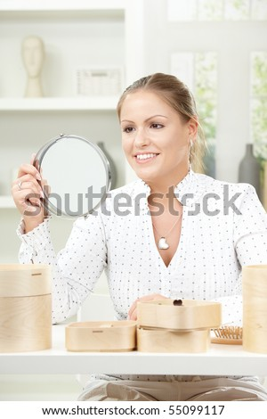 Beautiful young woman sitting at table, holding makeup mirror, smiling.