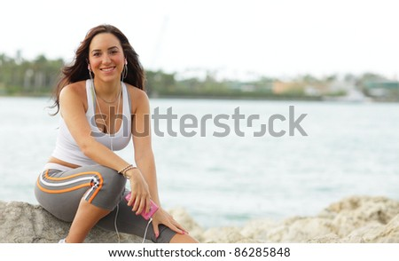Beautiful young woman sitting by the water