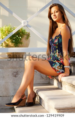 Beautiful young woman sitting elegantly on ���° stairs