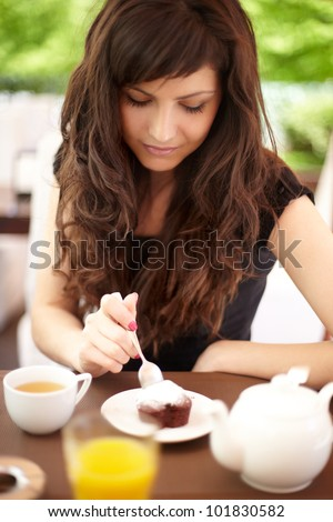 beautiful young woman sitting in a cafe eating cake