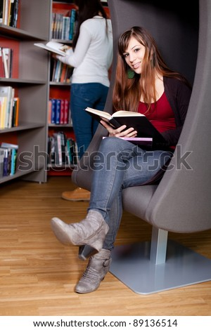 Beautiful young woman sitting in a lounge chair in the library reading a book