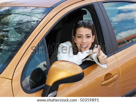 Beautiful young woman sitting in a new car with thumb up