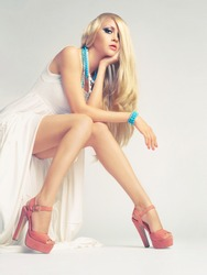 Beautiful young woman sitting in a trendy shoes