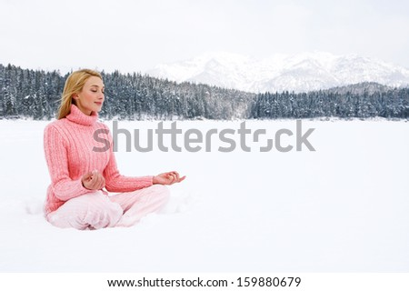 Beautiful young woman sitting in a yoga position on a frozen lake in the snow mountains landscape, meditating and contemplating the scenery during a winter day on holiday, outdoors.