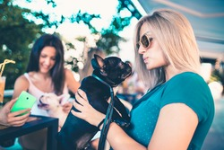 Beautiful young woman sitting in cafe with her adorable French bulldog puppy. Spring or summer city outdoors. People with dogs theme.