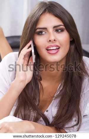 Beautiful young woman sitting in the bedroom and talking on the mobile phone.